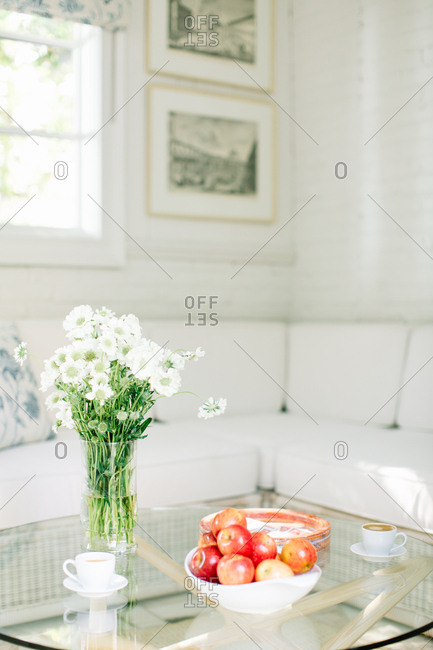 Bowl of apples and vase full of wildflowers on a glass-top table