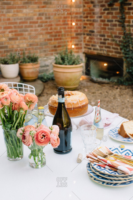 Bundt cake, fresh-cut roses and plates on an outdoor table