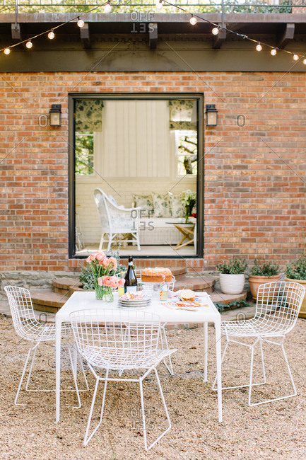 Outdoor dining table set with a bundt cake, plates and fresh-cut roses