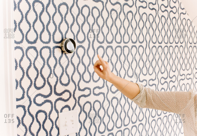 Woman reaching to touch a high-tech thermostat on a patterned wall