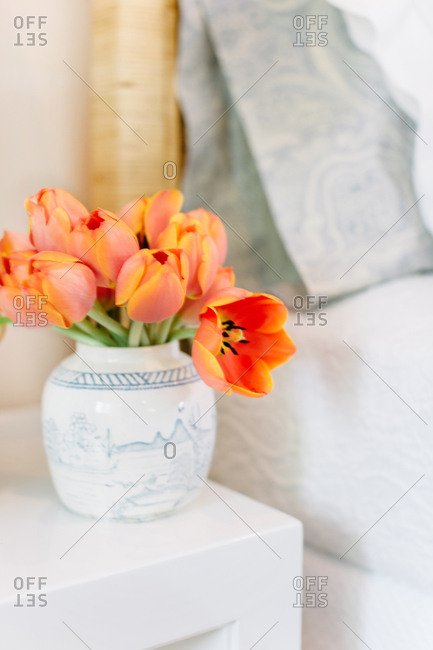 Coral colored flowers in a vase on a bedside table