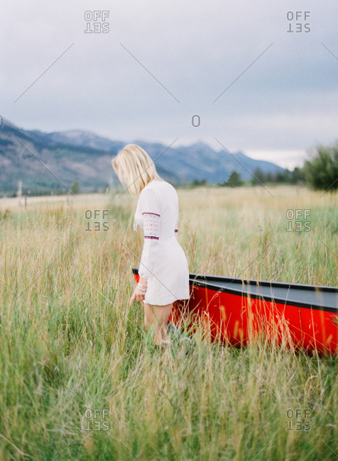 Woman pulling a canoe into a field