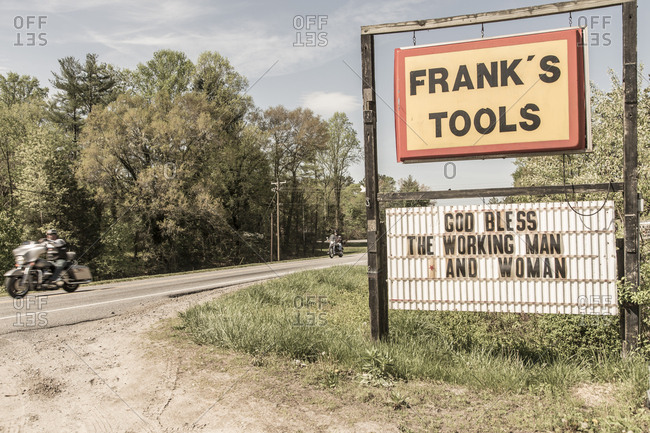 "North Wilkesboro, North Carolina - April 27, 2014: Shop sign with message reading ""God bless the working man and woman"""