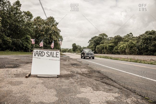 July 6, 2015: Yard sale sign with American flags on top