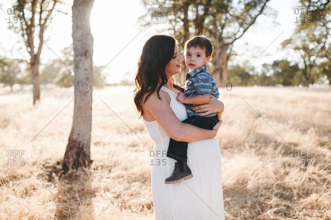 Pregnant woman lovingly holding boy