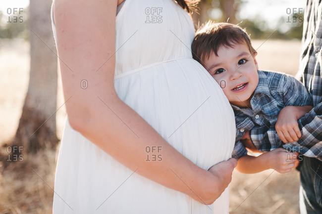 A toddler boy held between parents