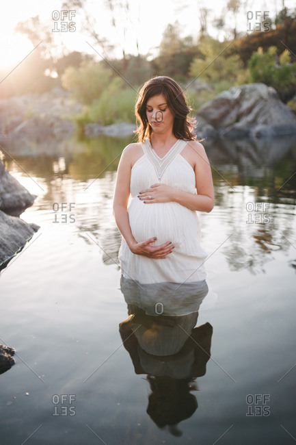 Pregnant woman holding stomach in water