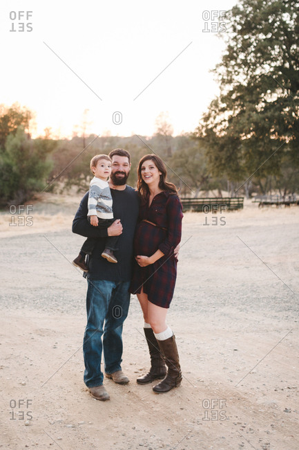 Expectant parents holding toddler boy