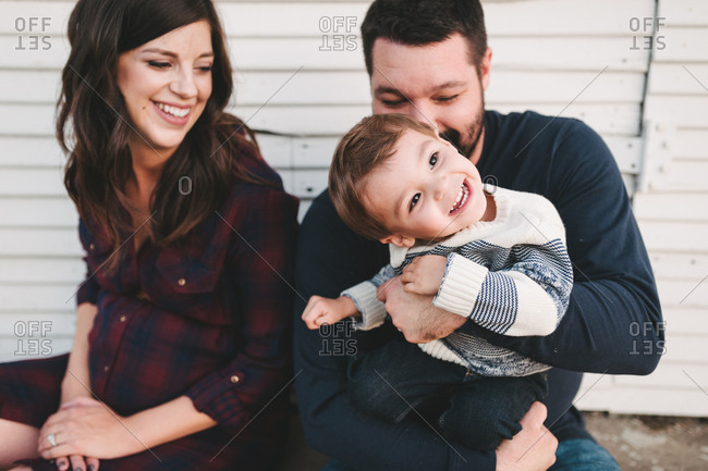 Expectant parents playing with boy