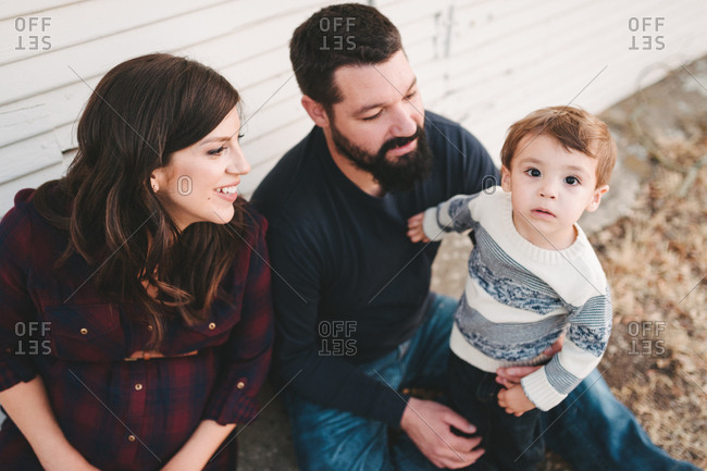 Expectant parents sitting with boy