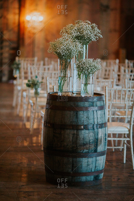 Vases of baby's breath on a rustic barrel near a wedding seating area