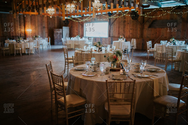 Tables set for a reception in a rustic, barn wood venue