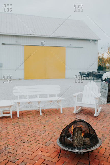Brick patio with a fire pit and benches near a barn