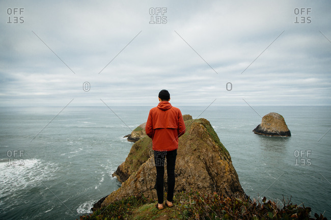 Man on ocean cliff from behind
