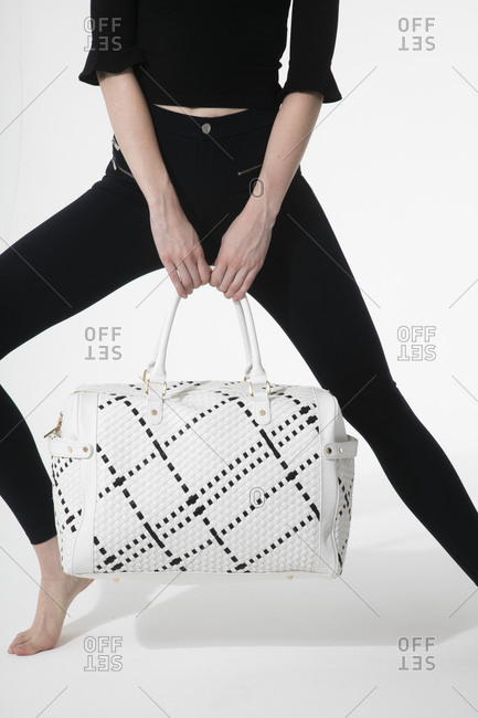Woman in all black holding a large white handbag