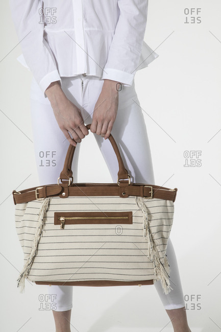 Woman in all white holding a large striped handbag