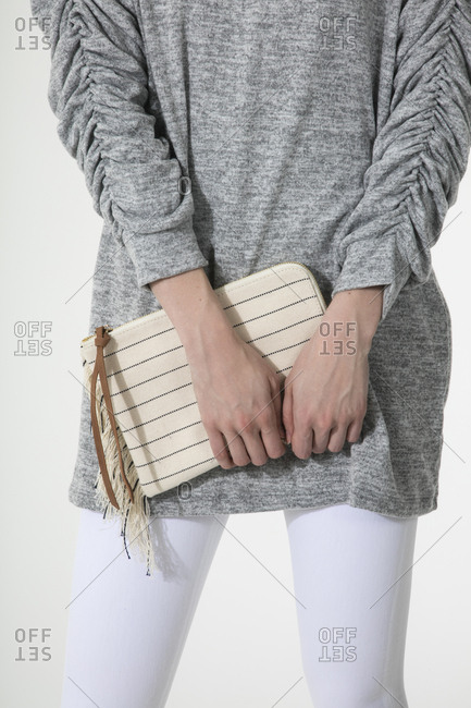 Woman in a gray sweater holding a striped clutch purse
