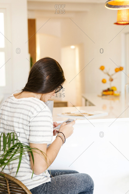 Woman using smartphone at kitchen counter