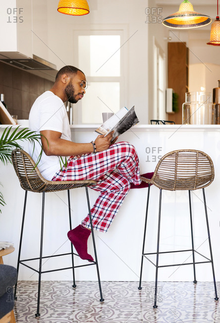 Man reading magazine at kitchen counter