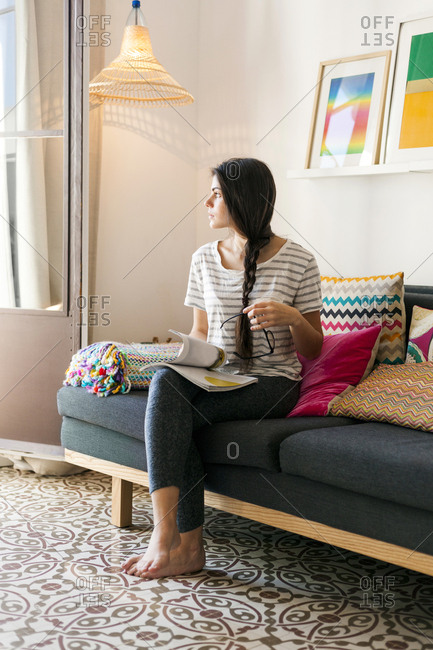 Woman gazes out window while reading magazine at home