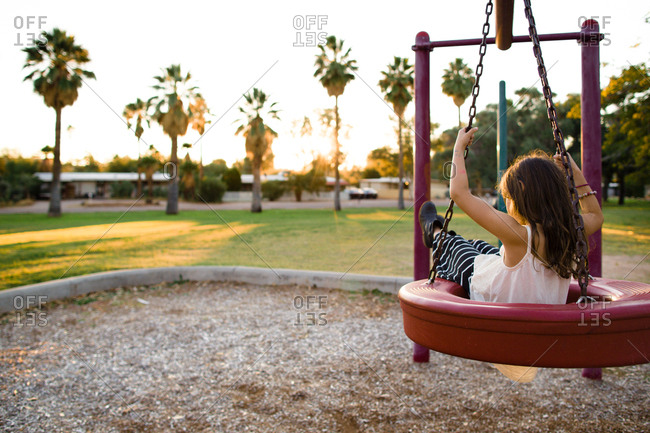 Young girl on tire swing at sunset