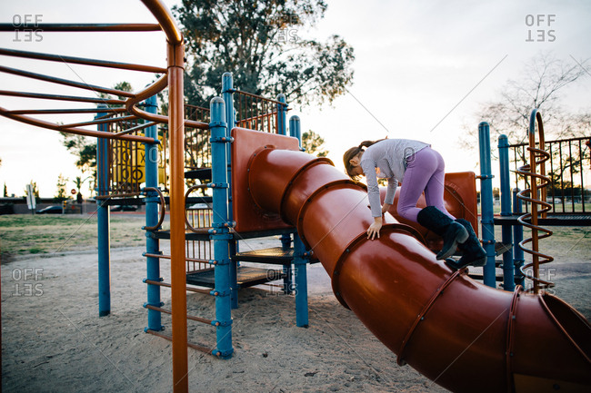 Girl climbing on playground slide at dusk