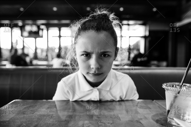 Portrait of a stern-faced girl at restaurant table