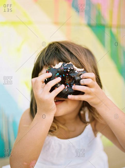 Girl holds a donut over her eye