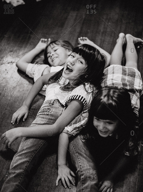 Overhead view of three young sisters lying on floor