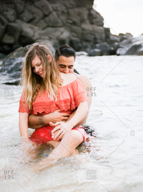 Man playfully lifts partner while they stand in the ocean