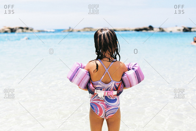 Back view of young girl wearing floatation vest at beach