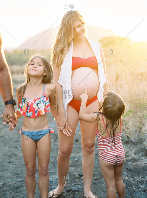 Toddler touching pregnant mother's belly while walking on the beach