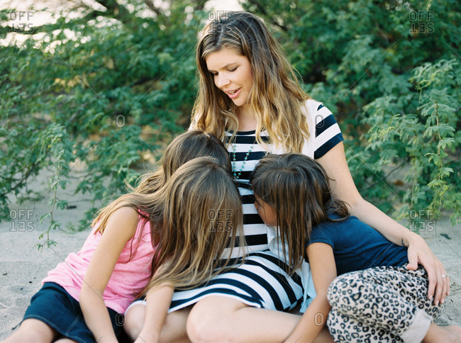 Daughters kissing mother's pregnant belly