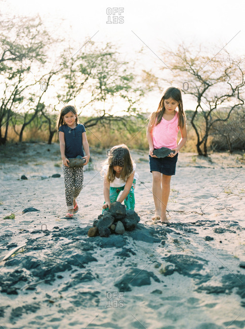 Three little girls stacking rocks into a pile on a beach