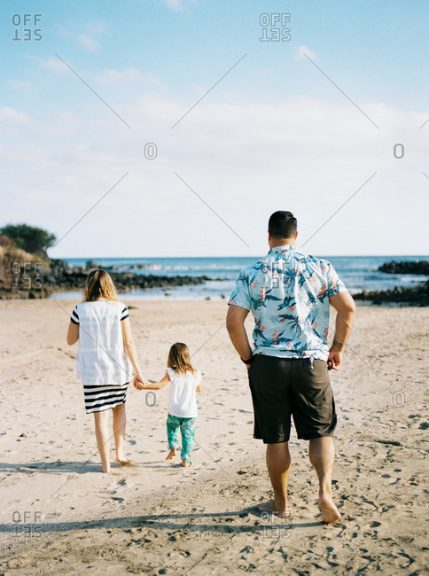 Couple walking on beach with toddler