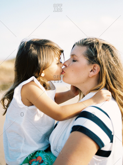 Mother kissing her daughter outdoors at sunset