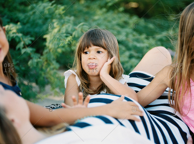 Young girls sitting by mother's pregnant belly and making silly faces