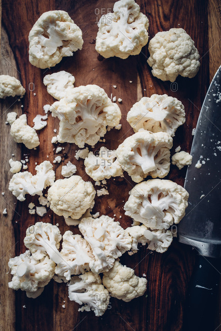 Chopped cauliflower on a wooden cutting board