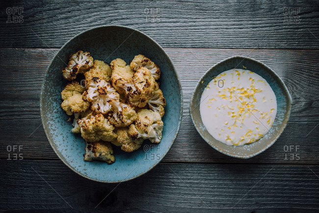 Blue dishes with cooked cauliflower and a lemon cream sauce on a wooden table
