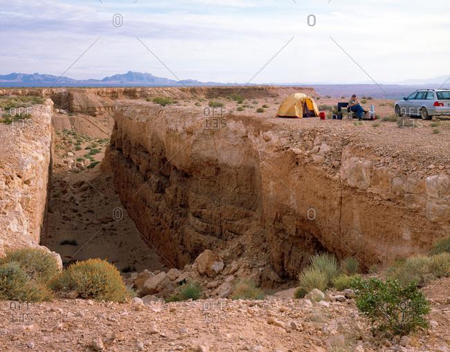 Man camping next to desert gorge