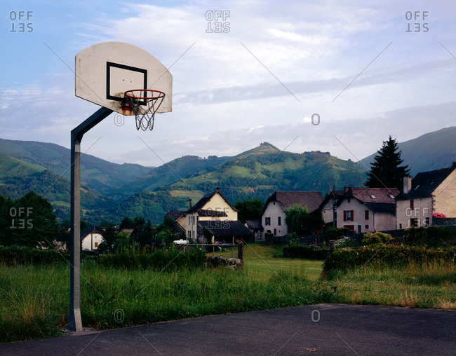 Basketball court near homes by mountains