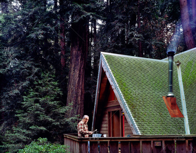 Man on porch of cabin in remote forest