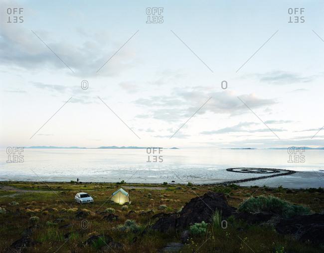 Campsite near a remote shore at dusk