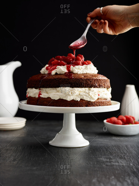 Drizzling sauce on strawberry cream cake