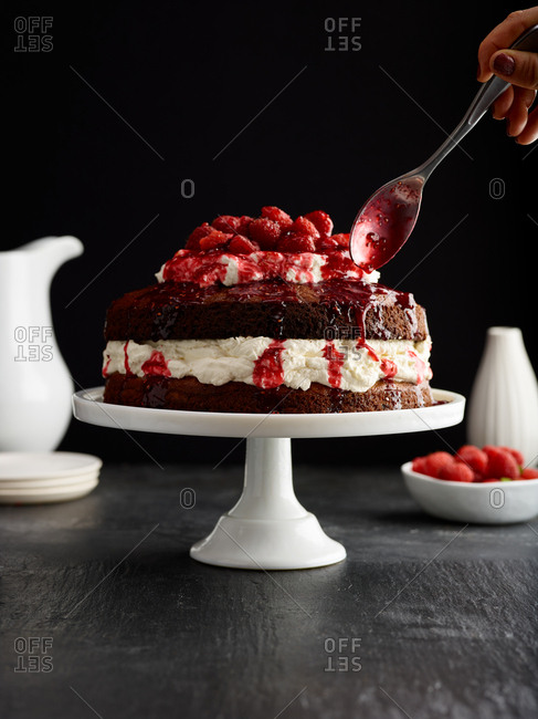Drizzling sauce on strawberry and cream cake