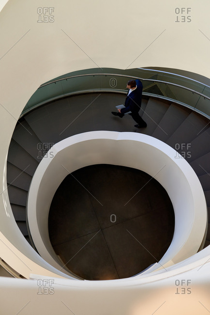 High angle view of businessman in suit going down the spiral stairs in modern business center