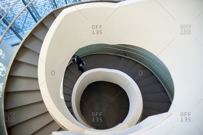 Businessman going down the spiral staircase in modern business center