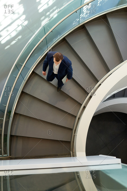 Directly above view of man in suit with laptop going down the spiral stairs in modern office building