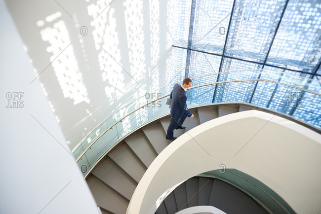 Confident businessman in suit going up the spiral stairway in modern office building with glass wall