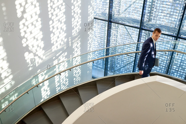 Young pensive businessman in suit going up the curved stairs and looking to the side